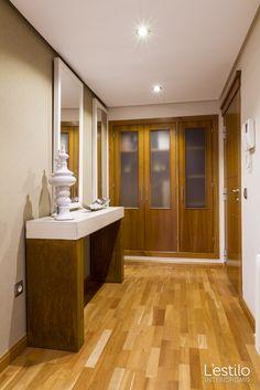 Entrada con consola de diseño minimalista y   acabados en madera natural.