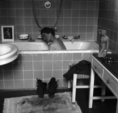 Lee Miller in Hitler's apartment at 16 Prinzregent Note the combat boots on the bath mat now stained with the dust of Dachau; and a photograph of the previous owner of the flat propped on the edge of the tub. - 2246 | LeeMiller