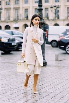 Miroslava Duma wearing a turtleneck, midi skirt, long double-breasted vest, white structured bag + white pointy heels