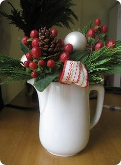 I only bought the hypericum berries and spruce and used the other  accessories from my Christmas stash. The pinecones, small bulbs  and ribbon are wired and plucked in the arrangement. By A Country Girl In The City