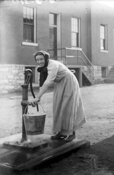 woman using a water pump in a South St. Louis neighborhood. (1910)