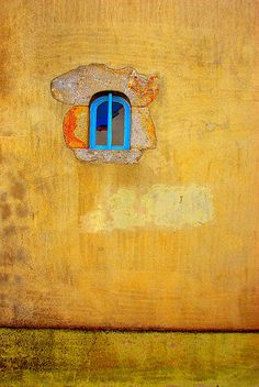 blue window in yellow wall