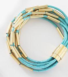 Complementa tu set de accesorios con ésta pulsera de cordón verde aqua con detalle de barras tubulares en 4 baños de oro de 18 kt. Modelo 415927.