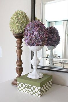fake hydrangeas hot glued to large plastic Easter eggs sitting on wooden candle holders