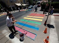 Municipality workers paint a pedestrian crossing in the colors of a rainbow flag before the start of the annual gay pride parade in Tel Aviv on June 8, 2012. (Amir Cohen/Reuters)