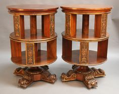 A pair of early 20th Century Neo-Classical Revival walnut and parcel gilded circular revolving library bookcases, each fitted with two revolving tiers with relief moulded reserve panels decorated with portrait medallions