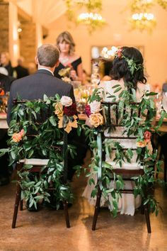 Simple greenery and a few pops of florals creates a beautiful setting for the brides and groom! Photo by Taylor Lord #bridesofaustin #weddings #chairtreatment