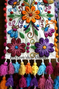 Sheep wool runner hand embroidered with graceful flowers and leafs, finished with multicolored tassels. Gorgeous at your dinner table or as a bed runner. The vibrant colors and detailed motives will make any room look beautiful! The pictures are from the actual item you will receive ! Please note that color variations and small imperfections are natural in handmade items. Measures 72 in long x 12 inch wide Color Cream