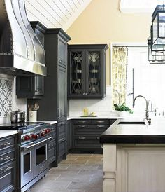 Traditional Home. Amy Bergman - Beautiful charcoal gray black kitchen design with charcoal gray black kitchen cabinets with marble counter tops, mosaic tiles backsplash, iron studded kitchen hood, subway tiles backsplash, white washed kitchen island with butcher block counter top, kitchen island lanterns and butter yellow walls paint color.