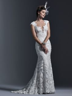 Sottero and Midgley - VIDONIA, Dramatic laser cut lace appliqués lay atop tulle in this form-fitting sheath wedding dress; with demure illusion back. Finished with plunging neckline and covered buttons over zipper closure.