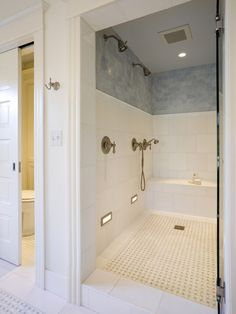 Huge shower with bench and multiple shower heads. Pocket door on toilet room to save space