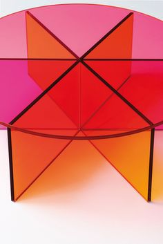 XXX design Johanna Grawunder   Low table realized in transparent pink, orange and yellow coloured glass. The base is obtained by gluing six laminated, 6+6 mm. thick glass plates with special chamfering. The top, in laminated 6+6 mm. thick glass, leans on the base and is available in one of its three colours.