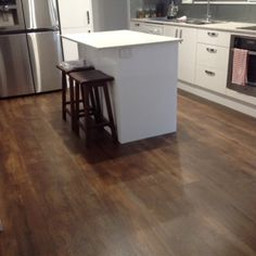 Luxury Vinyl Planks - dark colours look classic against a white kitchen - add some class to your floors today.