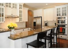 A light, bright kitchen with granite countertops and stainless steel appliances.