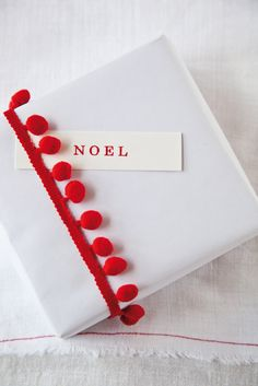 Simple white gift wrap with red pompom trimming.
