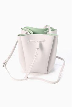 YAHKI ダブルフェイスバゲットバッグ  YAHKI ダブルフェイスバゲットバッグ 18144 2016SS La TOTALITE 今年のトレンド巾着型のデザインです 裏面にもカラーが施されており表地とのコントラストが楽しいバッグです 可愛らしい丸いフォルムはスタイリングのアクセントに ヤーキ 2014年スタートの日本ブランド 年齢や職業にとらわれない自由でお洒落な女性達により素敵なLIFEを送ってもらいたい そんな思いから生まれたブランドです