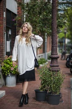 Rebecca Laurey is wearing an oversized top from & Other Stories, lace trimmed dress from ASOS, bag from Delvaux and boots from H&M