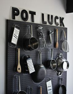 "DIY pots and pans pegboard w/ vintage letters spelling ""Pot Luck"" over the pegboard."