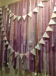 DIY Photo Booth back drop for our engagement party - made of ribbons, tulle, organza and the ever inexpensive plastic table cloths cut into strips, and attached to a curtain rod.  The gorgeous bunting was custom made by the very helpful Rhiana from ZestAndLime on Etsy.