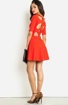 Fit and flare dress featuring short sleeves, v-neck, open crisscross back, and an exposed back zipper.