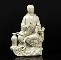 CHINE - XXe siècle Groupe en porcelaine émaillée blanc de Chine, Guanyin assis sur un rocher posé sur des vagues et tenant un sceptre. H.44 cm