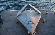 Sailors move an X-47B Unmanned Combat Air System (UCAS) demonstrator onto an aircraft elevator aboard the aircraft carrier USS George H.W. Bush (CVN 77).