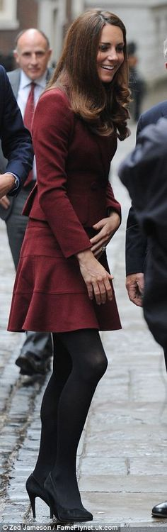 The duchess chose a short burgundy skater skirt and matching jacket by designer Paule Ka with thick black tights and heels