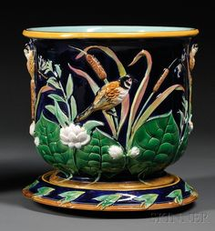 George Jones Majolica Jardiniere and Undertray, England, c. 1865-77, the deep blue ground with high relief marsh scene of birds, lily pads, bulrushes, and dragon flies, the undertray with leaf and twig decoration, each with impressed factory mark, total ht. 13 5/8 in.