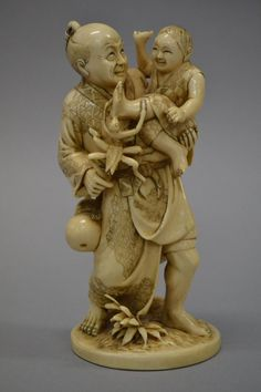Fine antique Japanese carved ivory Okimono of a man holding a child with a large insect biting his foot, seal mark to base, approx 15cm H