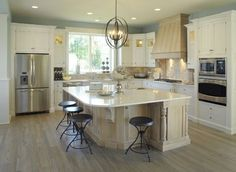 Kitchen with white cabinets, aqua walls, tan backslash and pale stained wood island -- Weaver Custom Homes, weavercustomhomes.com