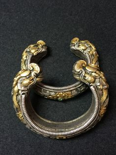 A pair of solid cast bangles, partially gilded, carved in dragon and floral motifs, fine chasing and ring-matting work. Bhutan, 19th c