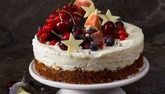 No-bake creamy lemon cheesecake with a spicy ginger nut biscuit base beautifully adorned with fresh summer fruits.