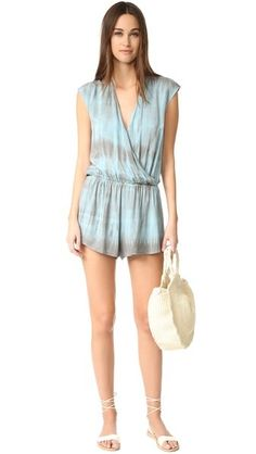 A slouchy Blue Life romper with a surplice neckline and soft tie-dye color. Gathered elastic waistband. Sleeveless.