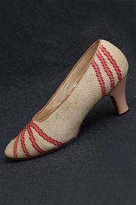 Needlepoint shoes, 1930s. Uppers were made from beige needlepoint with rose colored stripes across the toes and heels. The heels are pink leather.