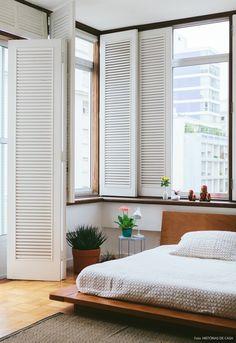 Completamente reformado, esse quarto tem uma parede inteira de venezianas pintadas de branco. Um charme!