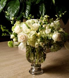 beautiful white and green centerpiece in glass urn container