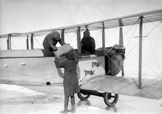 Alcohol is unloaded from an airplane seized during a Prohibition raid. ca. 1920s