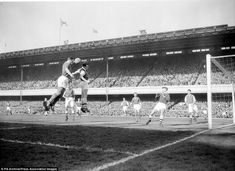 6th April 1957 : Leeds United legend John Charles out jumps Arsenel left back Dennis Evans at Highbury.