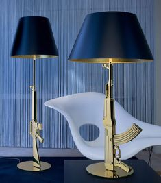 Philippe Starck : TABLE GUN table lamp providing direct reading and ambient lighting. Body is die cast aluminum with an overmolded polymer coating. Shade is plasticized paper. Comes in combination of gold/black or chrome/white.