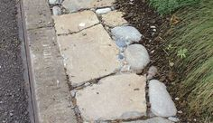 3. Pebbles fill the spaces between large flat stones in this edging along a streetside curb.