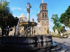 Hoy voy a hablar sobre una construcción típica mejicana, un Zócalo, que es una plaza central en las ciudades de México. Fuera de México, la gente llama a las plazas 'la plaza de armas'. En un Zócalo se encuentran principalmente tiendas, una iglesia o una catedral y los edificios gubernamentales. El Zócalo más famoso es la Plaza de la Constitución en la Ciudad de México, pero también hay una gran plaza en Puebla. Esta plaza es conocida como Centro Histórico de la ciudad y hay muchos…