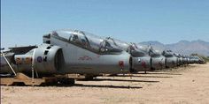 "Skeletal row of 74 RAF Harriers – minus wings and sophisticated nose-cones – stand propped up on wooden pallets in ""The Boneyard"" near Tucson, Arizona."