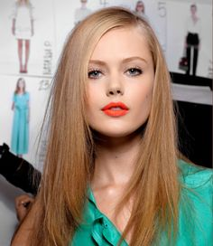 A bright matte lipstick, like this coral version, is super chic and modern.