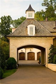 A Porte Cochere - a covered space that allows you to get in and out of a car and allows for the garages to be tucked into the back of the property.  What a great feature!!! Via Things that Inspire