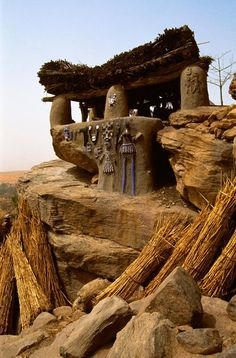 "Africa | Toguna Meetinghouse.  Mali | The Toguna house, decorated with relief carvings of ritual dance masks, is the meeting place for male elders.  Its thick thatch provides a cool resting-place for the Dogon elders, protecting them from the head of the midday sun. ©Carol Beckwith & Angela Fisher. 1994, Publication ""African Ceremonies"":"