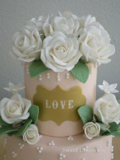 A closeup of my Gold, Love Plaque Cake with White Roses and Swiss Dots.