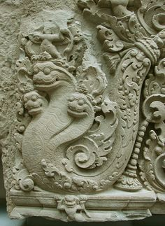 The Khmer dragon, or neak is derived from the Indian nāga. Like its Indian counterpart, the neak is often depicted with cobra like characteristics such as a hood. The number of heads can be as high as nine, the higher the number signifies rank. Odd headed dragons are symbolic of male energy while even headed dragons symbolize female energy. Traditionally, a neak is distinguished from the often serpentine Makar and Tao, the former possessing crocodilian traits and the latter possessing feline…