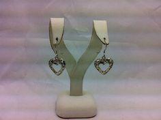 A pair of sterling silver heart dangle earrings.