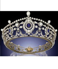 THE PORTLAND ANTIQUE SAPPHIRE, DIAMOND AND NATURAL PEARL TIARA. Designed as a series of twelve graduated cushion-shaped sapphire and old-cut diamond clusters to the openwork frame of diamond-set swag and husk motifs, embellished with bouton-shaped pearls and diamond line borders to the pear-shaped pearl finials and sapphire collet accents, mounted in silver and gold, circa 1890.