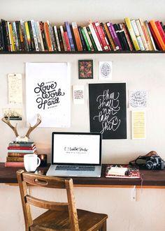 Prateleira comprida com livros acima da escrivaninha